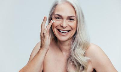 Woman applying anti aging cosmetic