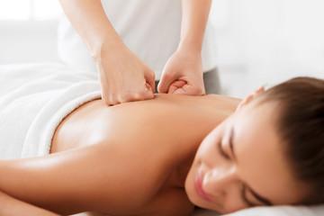 Professional therapist doing back massage to woman