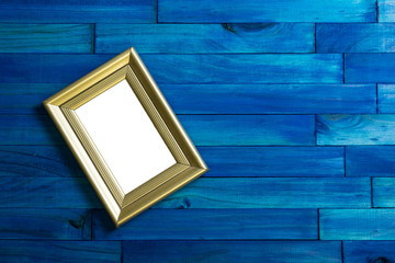 Gold picture frames on blue wooden background