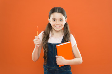 writing notes. kid diary. school girl read book on orange background. happy little girl with notebook. poetry and novel. modern education. literature lesson. back to school. Preparing to exams