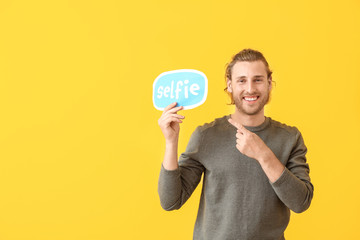 Male blogger holding paper with text SELFIE on color background