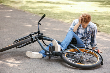 Young man fallen off his bicycle outdoors