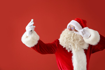 Portrait of Santa Claus taking selfie on color background