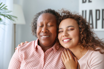 Portrait of African-American woman with her daughter at home