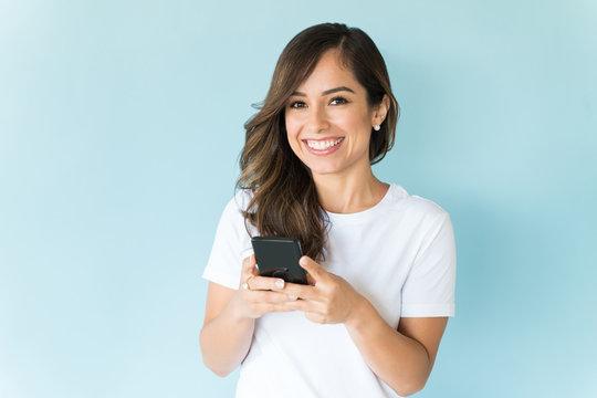 Happy Female Texting On Mobile Phone In Studio