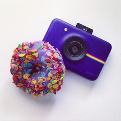 Purple Polaroid camera under a cereal covered purple donut