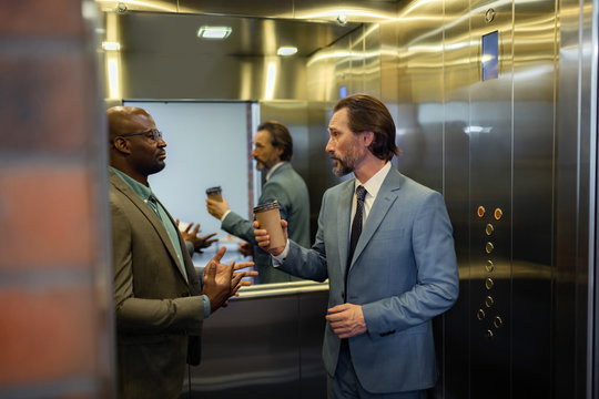 Grey-haired man talking to colleague while standing in elevator