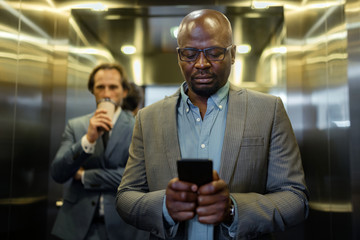 Dark-skinned young businessman reading message on smartphone