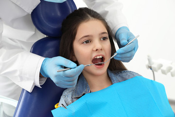 Professional dentist working with little girl in clinic