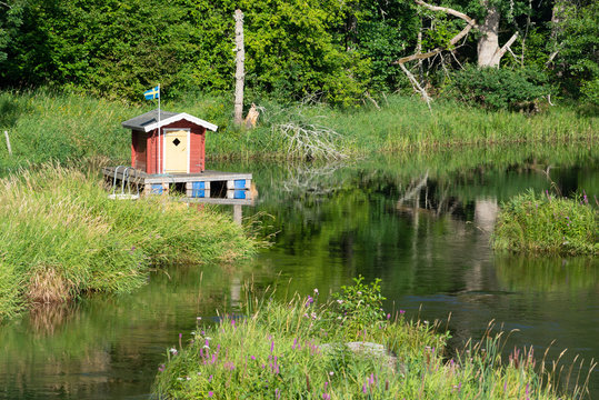 Small red wooden house on a boat dock at the small river Emån near Högsby  in southeastern Sweden in summer