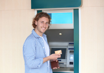 Fototapeta Young man with credit card near cash machine outdoors