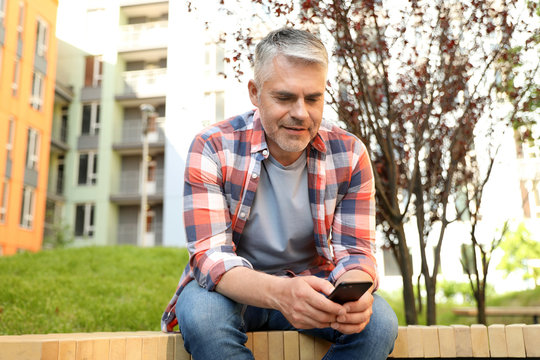 Handsome mature man using phone in park