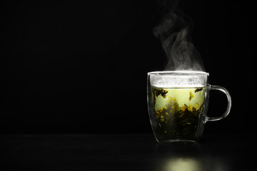 Glass cup of hot green tea on table against black background, space for text Wall mural