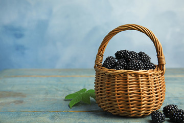 Wicker basket of tasty blackberries on blue wooden table, space for text Wall mural