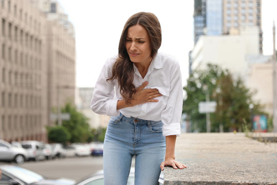 Young woman having heart attack on city street