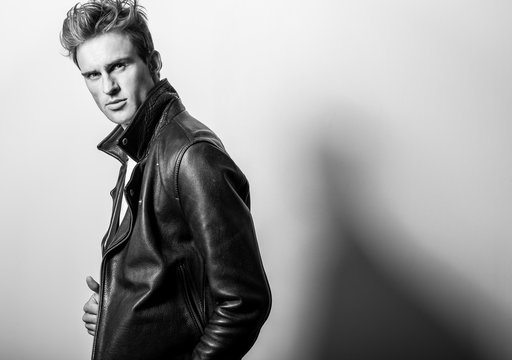 Handsome young man in classic leather jacket. Black-white studio portrait.