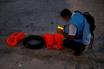 A member of Frontex takes pictures of a float and life-vests of migrants, after they arrived on a rescue boat at the port of Malaga