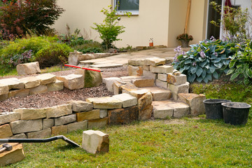 Stone steps and dry stone wall under construction  -   landscaping works with natural stones