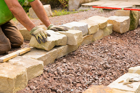 Man landscaping with natural stones -  Building of a dry stone wall