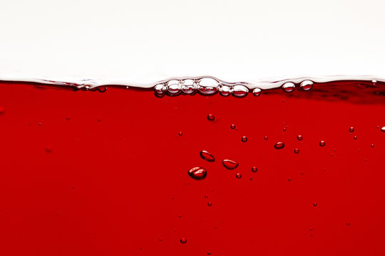 red bright liquid with bubbles on surface isolated on white