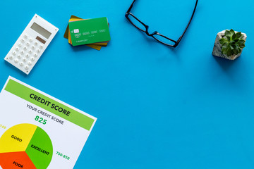 credit score with credit cards and calculator, glasses on banker work place blue background top view mock up