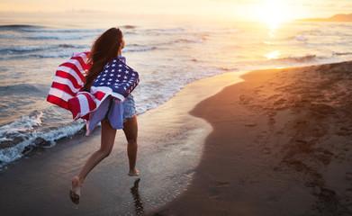 Cheerful happy woman outdoors on the beach holding USA flag having fun.