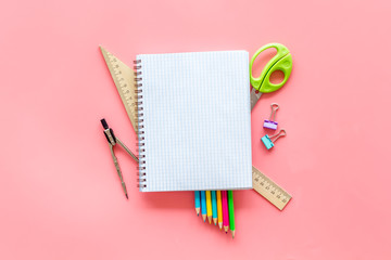 Back to school with stationary, notebook and scissors on pink student desk background top view...