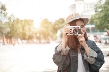 Smiling woman traveler with backpack holding vintage camera on holiday in thapae gate landmark chiang mai thailand,relaxation concept, travel concept Fototapete