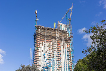 high-rise buildings under construction. Big construction site with cranes and scaffolding