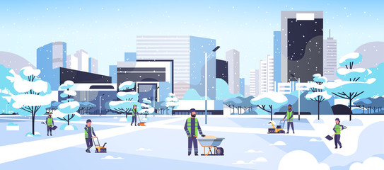 cleaners team using different equipment and tools snow removal concept men women in uniform cleaning winter snowy park cityscape background flat full length horizontal