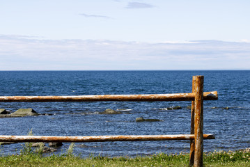 A perch fence in front of the dark blue sea and a light blue sky.