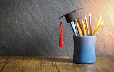 Education and back to school concept with graduation cap on pencils colour in a pencil case on dark