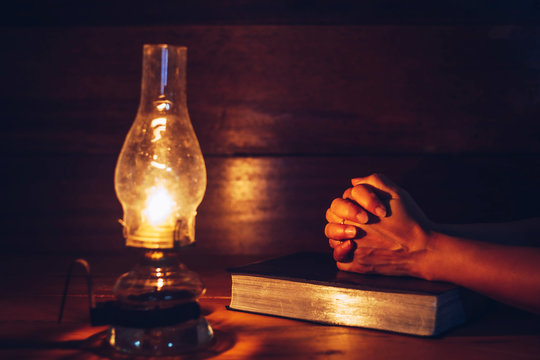 Close up of woman hands praying on bible with oil lamp on wooden table in dark room, Christian faith concept background
