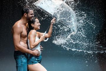 happy bearded man hugging cheerful girlfriend holding umbrella near splash of water on black