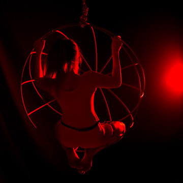silhouette of sexy female dancer in red light on a dark background. leggy woman in a bodysuit with metal rings. night club concepte