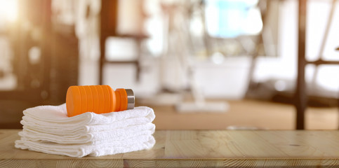 Towels and orange sport bottle with gym background