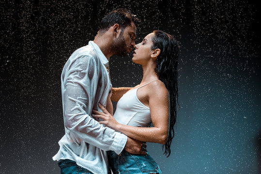 side view of handsome man kissing sexy wet girlfriend under raindrops on black