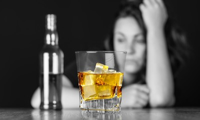 Drunk Woman At Bar Counter with a Bottle and a Glass of Whisky