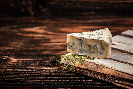 Blue cheese close up on an old wooden table. horizontal macro. mold. free space for text