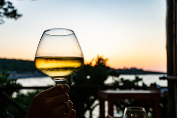 a glass of white wine at sunset