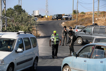 Israeli soldiers and a member of Zaka Rescue and Recovery team work near the scene where the Israeli military said an Israeli soldier was found stabbed to death near a Jewish settlement outside the Palestinian city of Hebron in the occupied West Bank