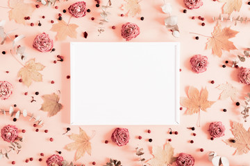 Autumn creative composition. Blank frame, eucalyptus, berries, leaves, roses, flowers on pastel pink background. Thanksgiving Day concept. Fall, autumn background. Flat lay, top view, copy space