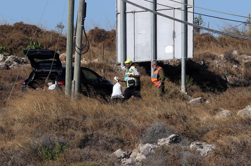 An Israeli soldier and a member of Zaka Rescue and Recovery team work near the scene where the Israeli military said an Israeli soldier was found stabbed to death near a Jewish settlement in the Israeli-occupied West Bank