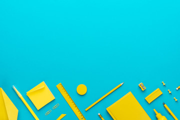 Top view photo of yellow stationery over turquoise blue background with copy space. Flat lay image of different stationary objects as back to school concept.