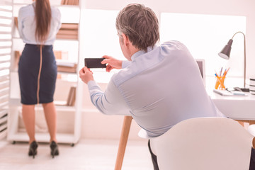 Boss secretly taking pictures of his secretary