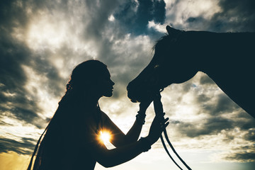 The girl with a horse. American Indian girl and horse at the silhouette. Concept of freedom.