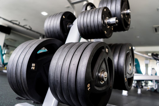 Sports equipment in gym Barbells of different weight on rack