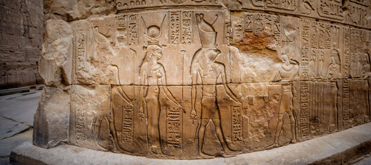Ancient Egyptian hieroglyphs and relief drawings on one of the walls of the Edfu complex. Temple of Edfu, Nubia, Egypt.