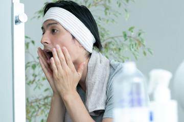 顔に化粧水を塗る男性