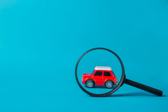 Red car peeked out with a magnifying glass on blue background. Technical inspection and machine search concept